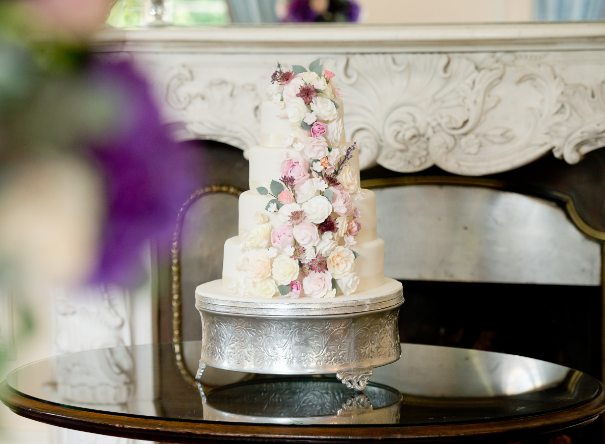 A white, tiered wedding cake with a cascade of pastel flowers down the front.