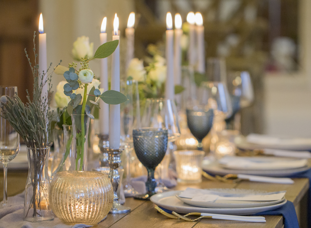 Close up of a table set up, blue glasses, muted flowers and lit candles