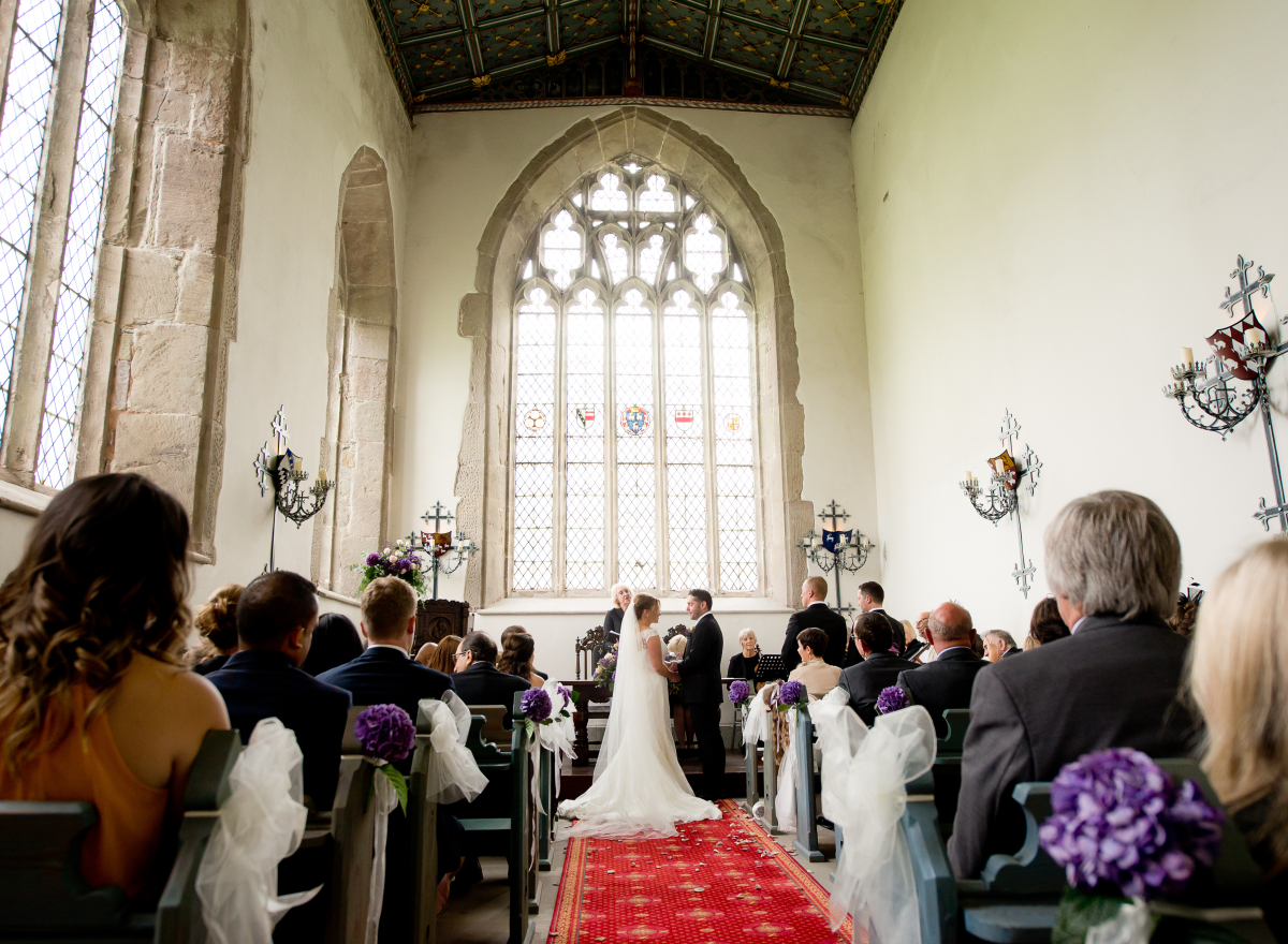 A couple face each other in a chapel. They are getting married.