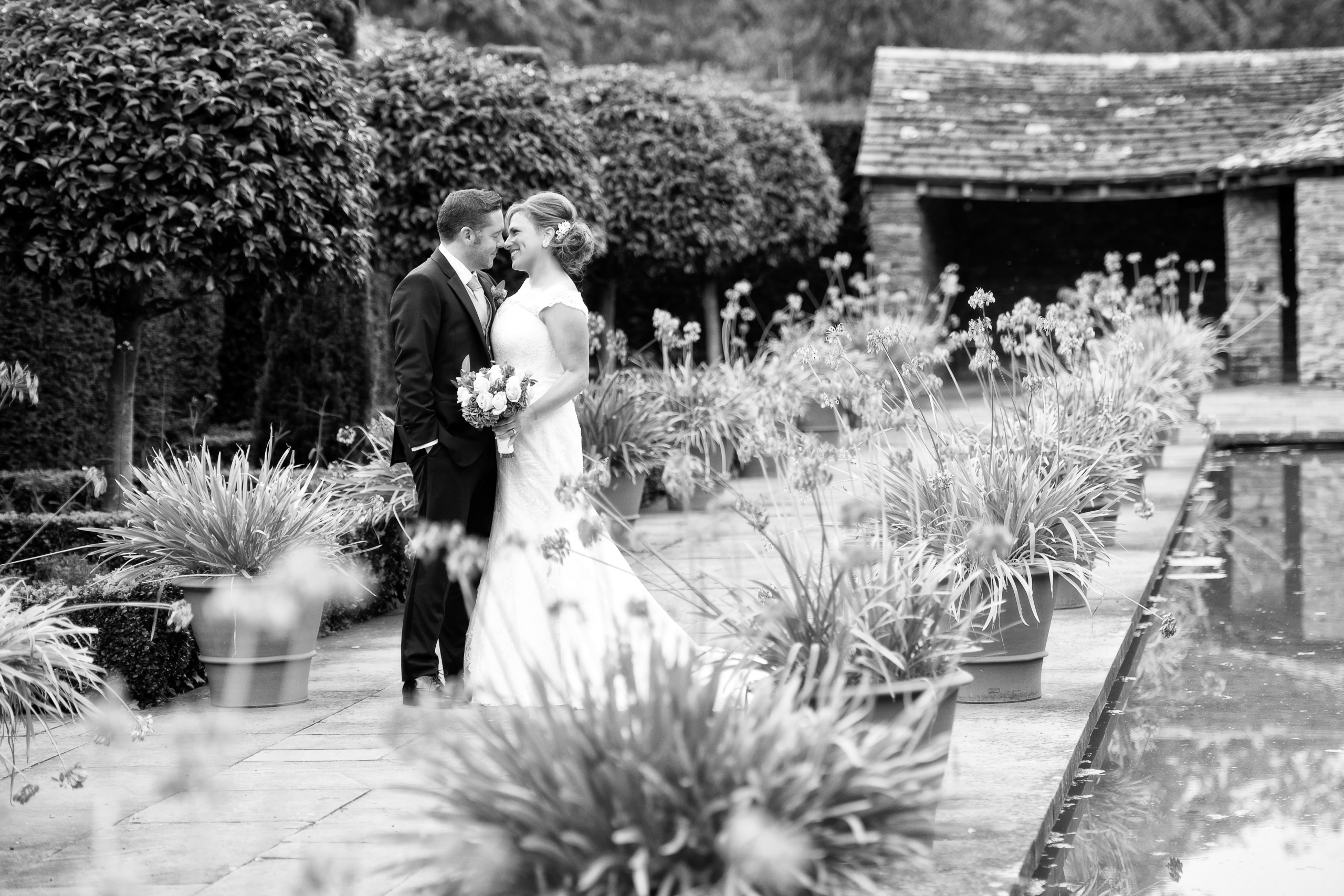 A black and white photo of a bride and groom with pots of flowers stretching alongside them.