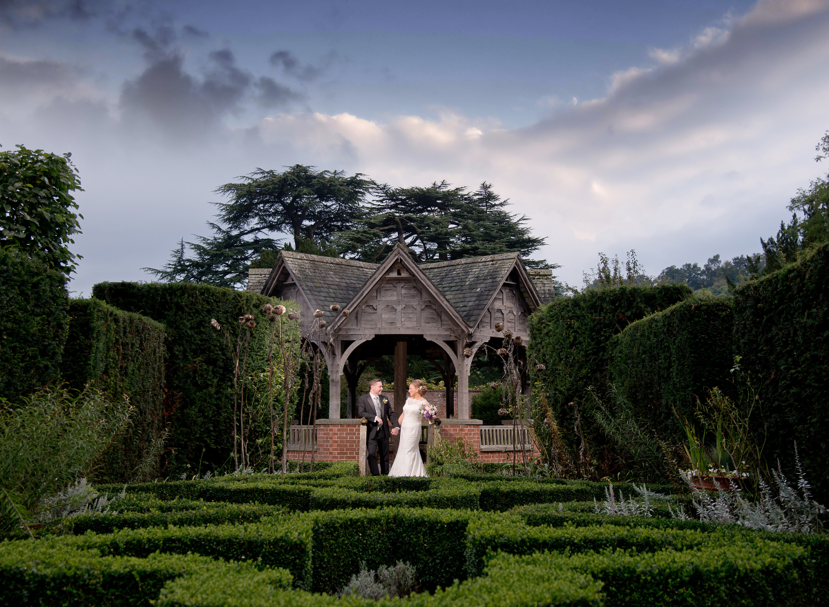 A couple in wedding attire, standing underneath a pavilion green hedging in front of them.
