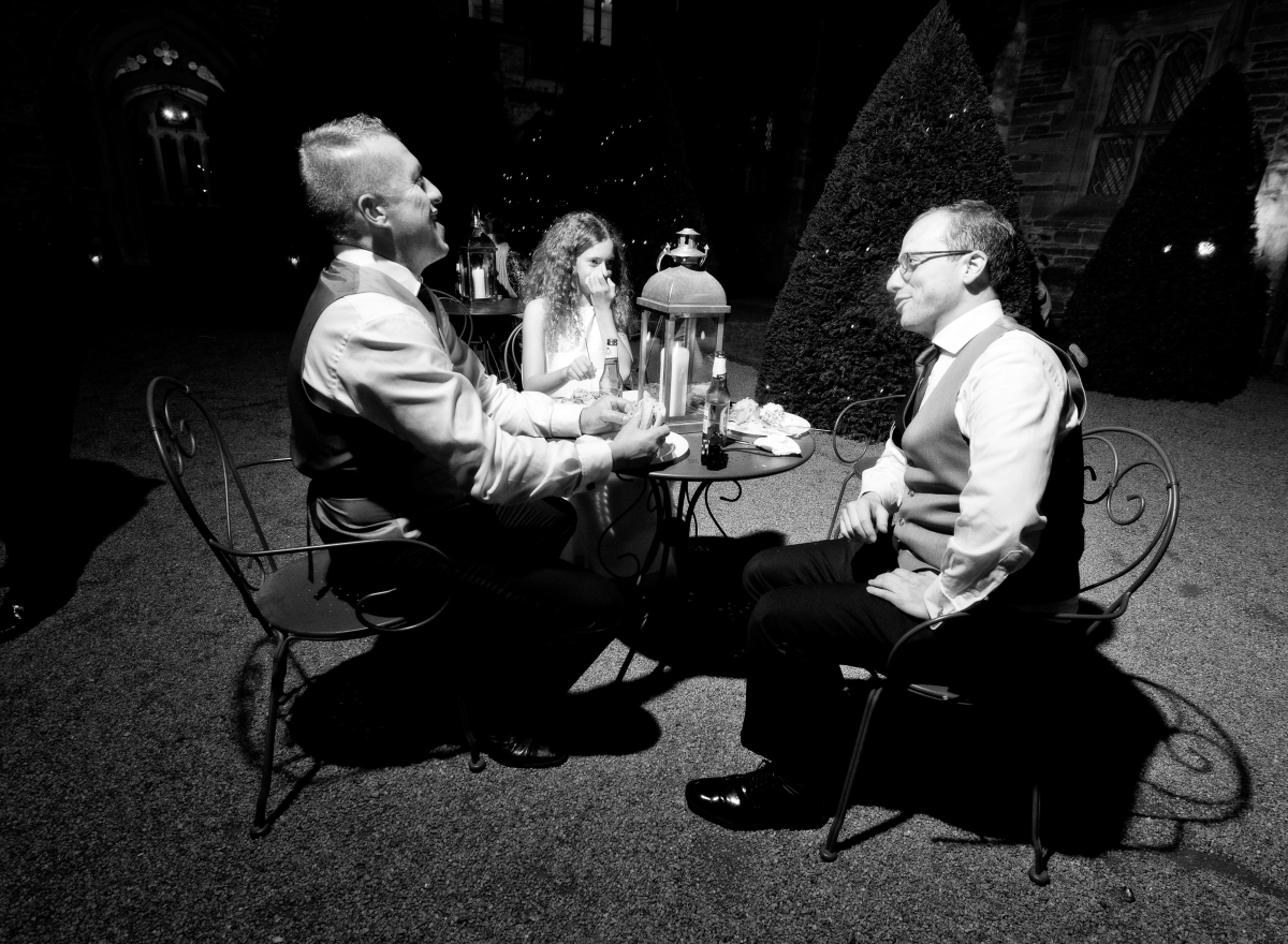 A black and white photo of three people sitting around a table eating