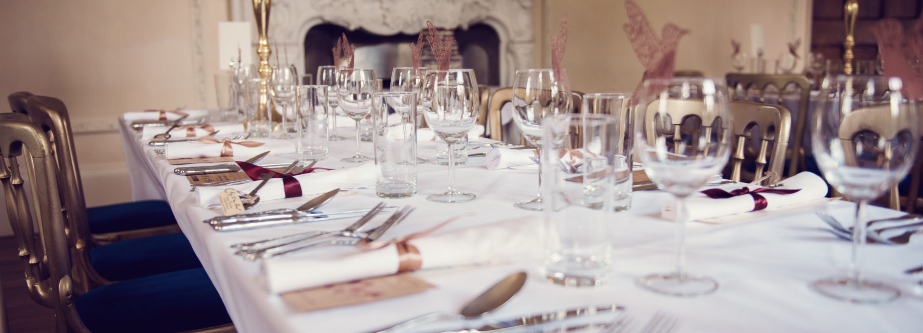A long table, laid out with glasses and cutlery