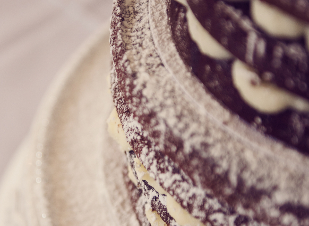 A close up of a chocolate wedding cake, dusted with icing sugar