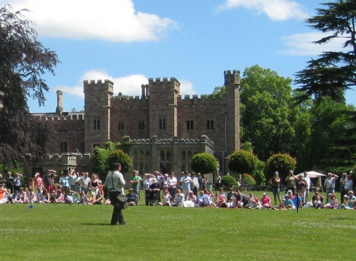 A crowd of people sitting on the grass in front of Hampton Court Castle