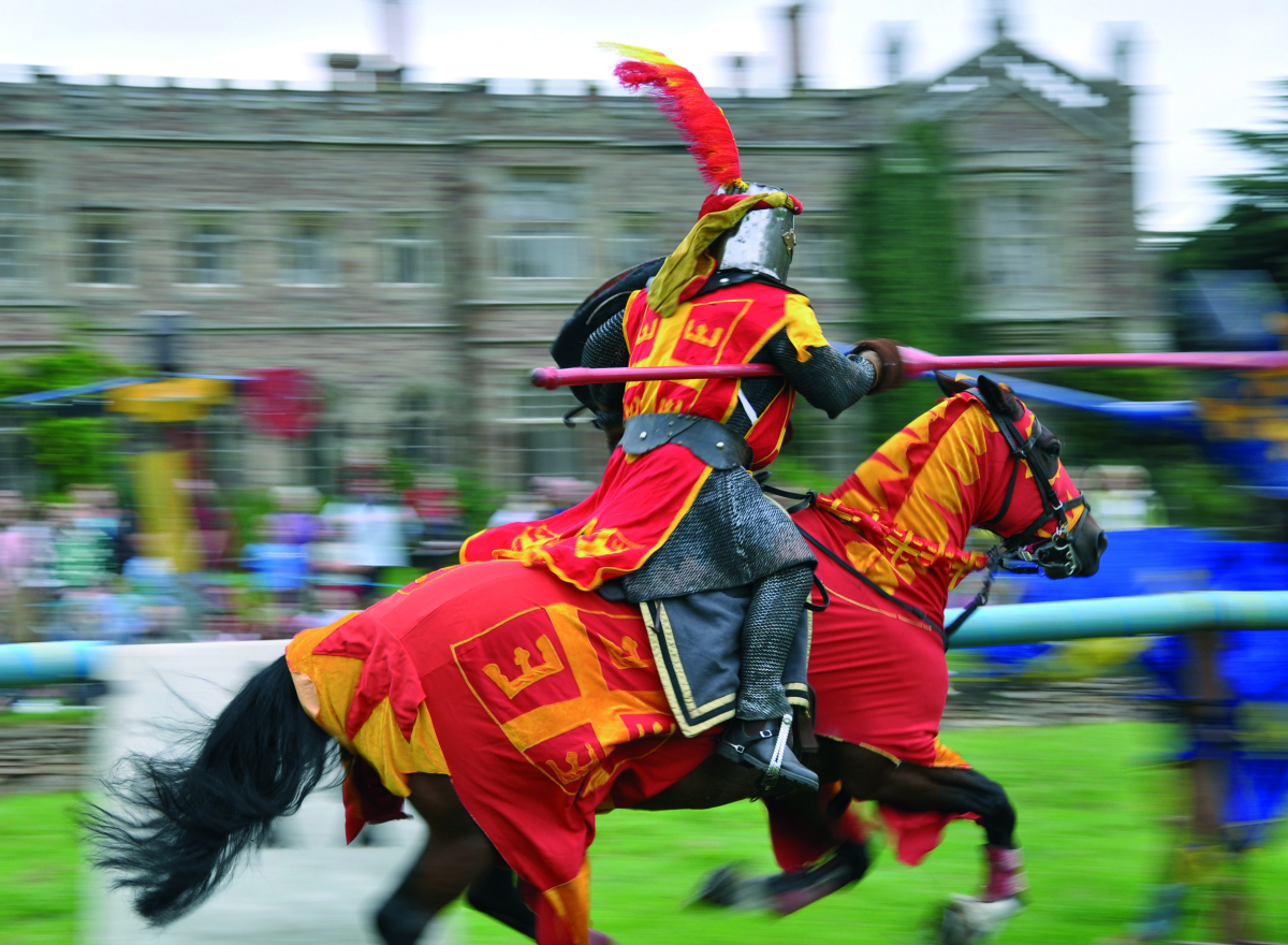 A knight in mail and red tabards jousting.