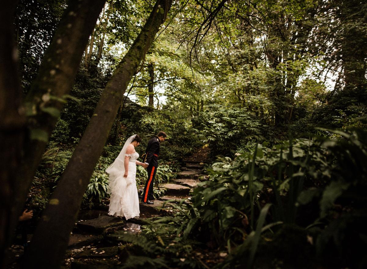 Wedding couple walking through leafy garden