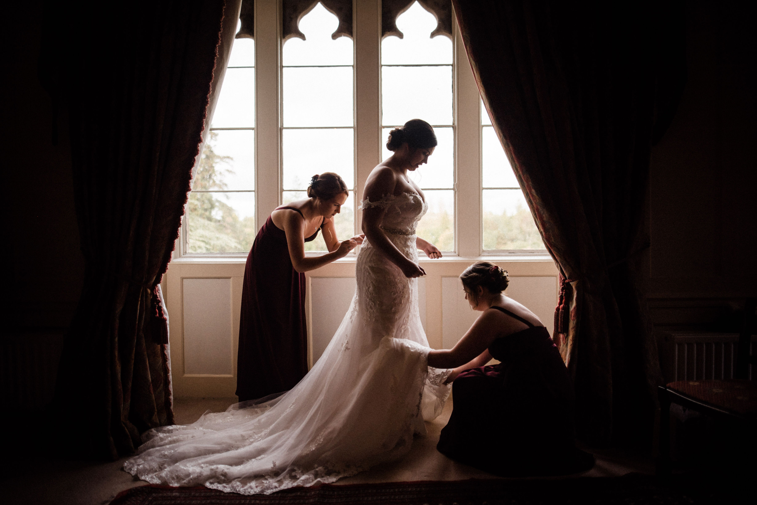 Bride and two bridesmaids in front of a large window