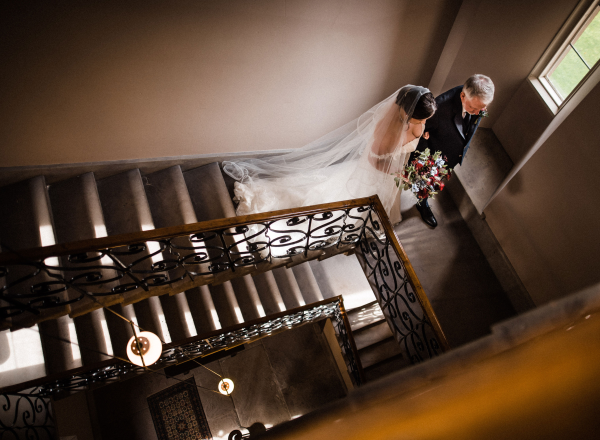 Bride and father of the bride walk down the cantilever staircase