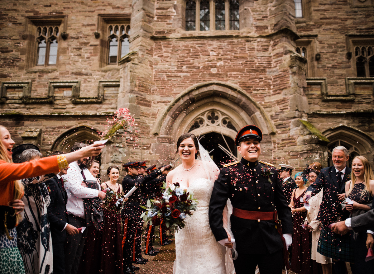 Couple in courtyard with guests throwing confetti
