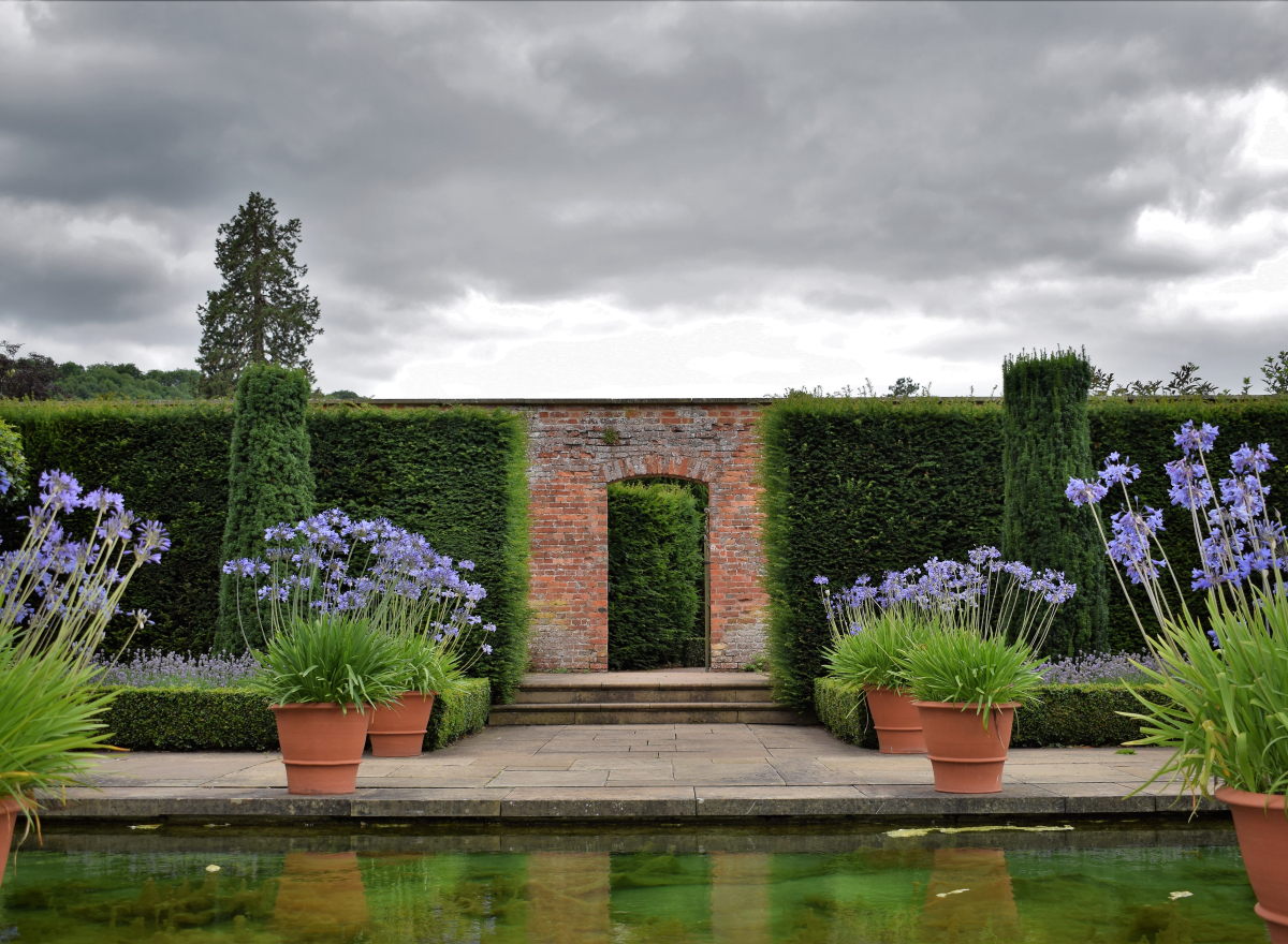 Doorway across water and paths with pots of purple flowers