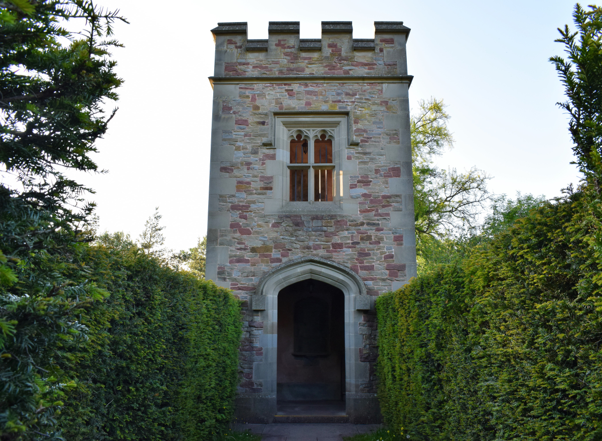 a gothic stone tower, with green hedges either side