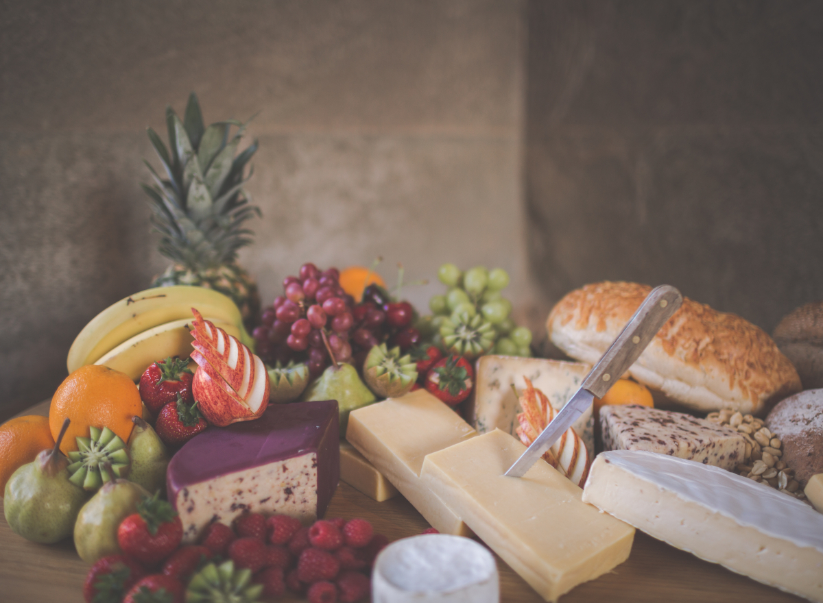 A cheese board piled up with fruit, cheese and bread.