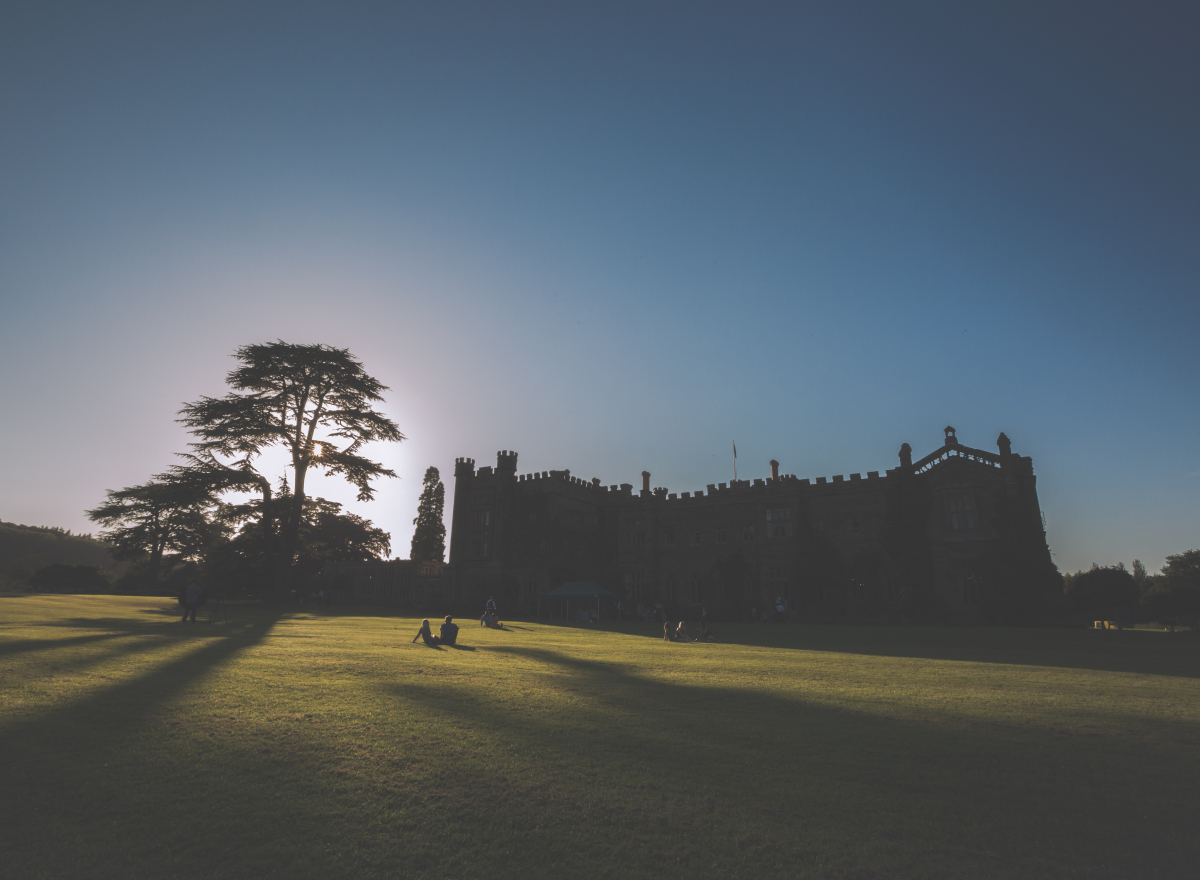 The sun sets over a castle, people sitting on the lawn in the forefround.