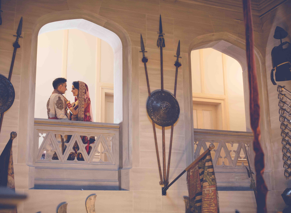 A couple looking into each other's eyes, standing in the archway of a balcony.