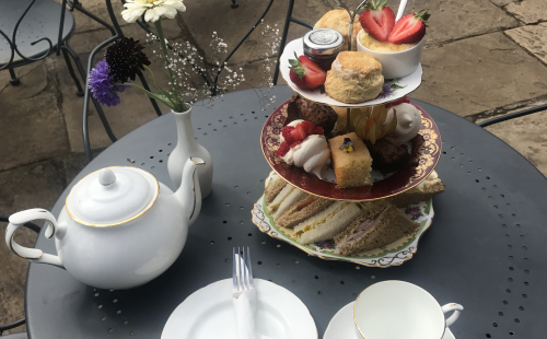 A table with tea pot, cup & saucer and afternoon tea on a cake stand