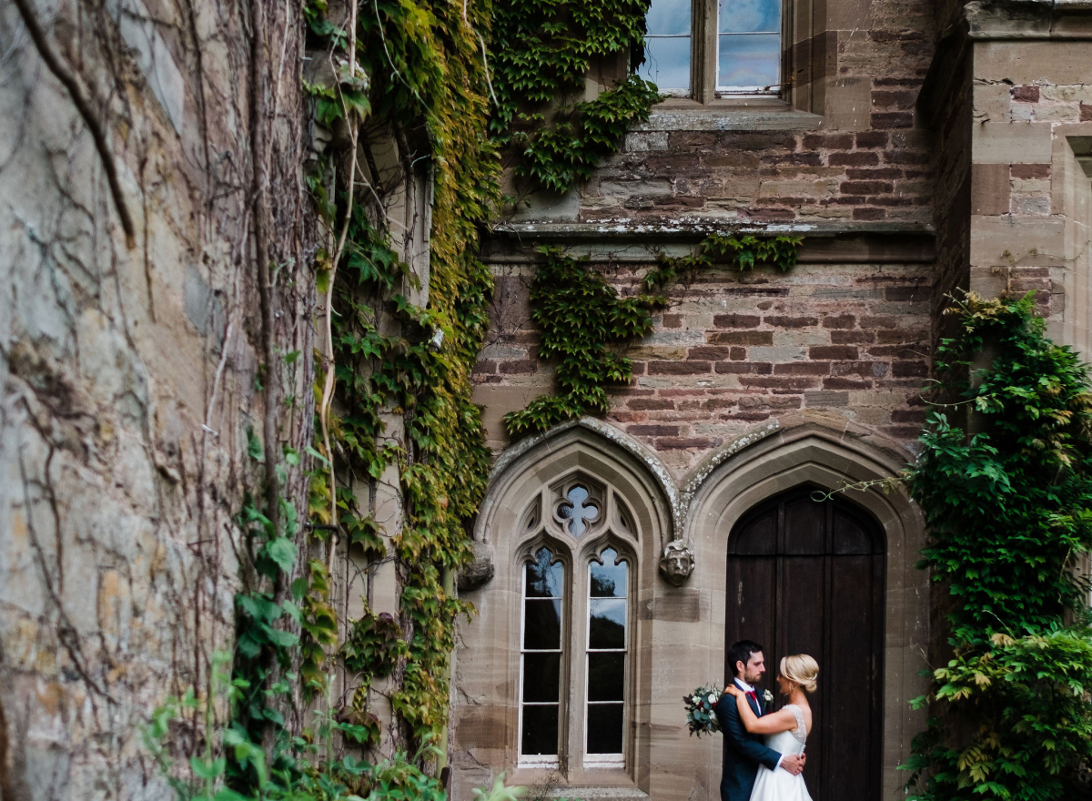 Couple standing on steps under castle wall and vines
