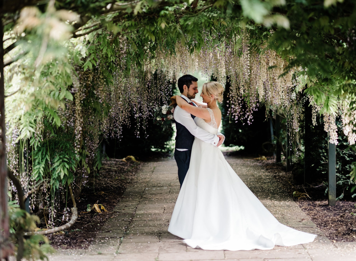 Wedding couple under the wisteria arch