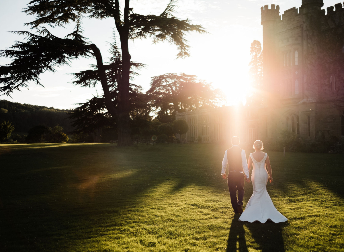 Wedding couple waling hand in hand across lawn in sunshine