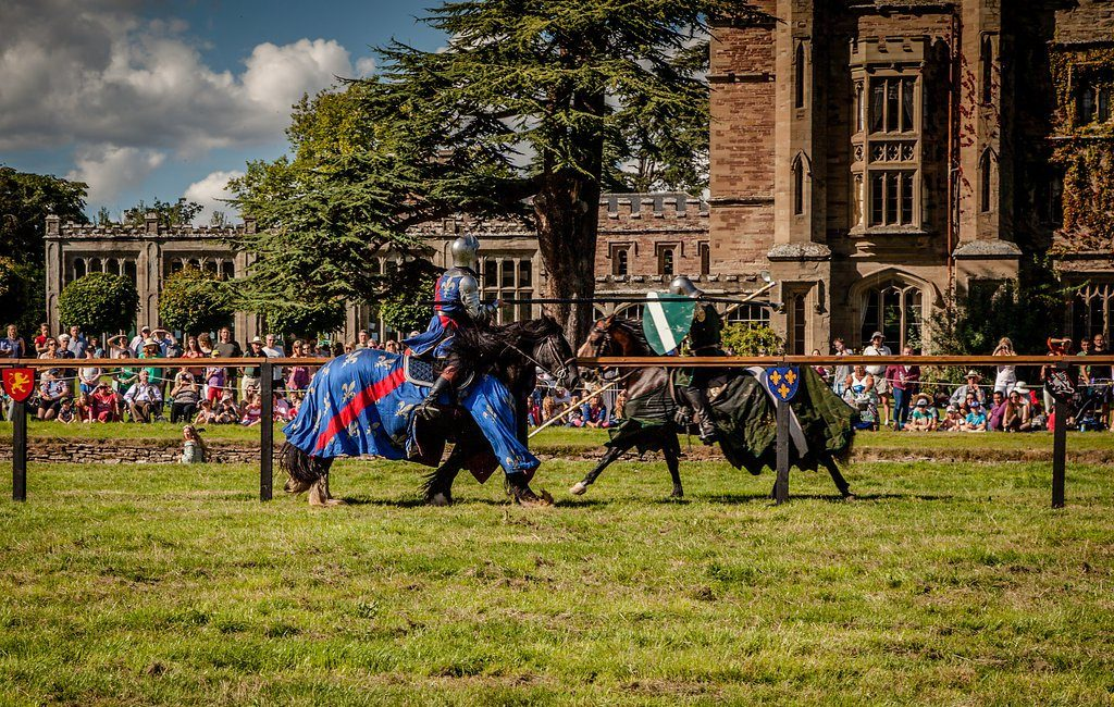 Two knights jousting in front of an audience