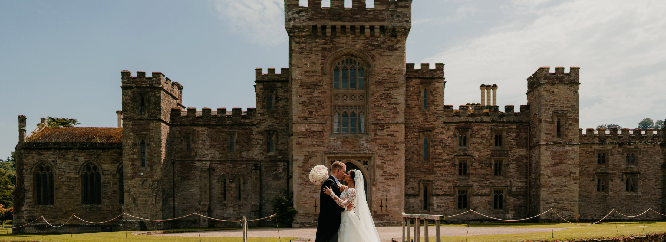 Wedding couple kiss in front of castle