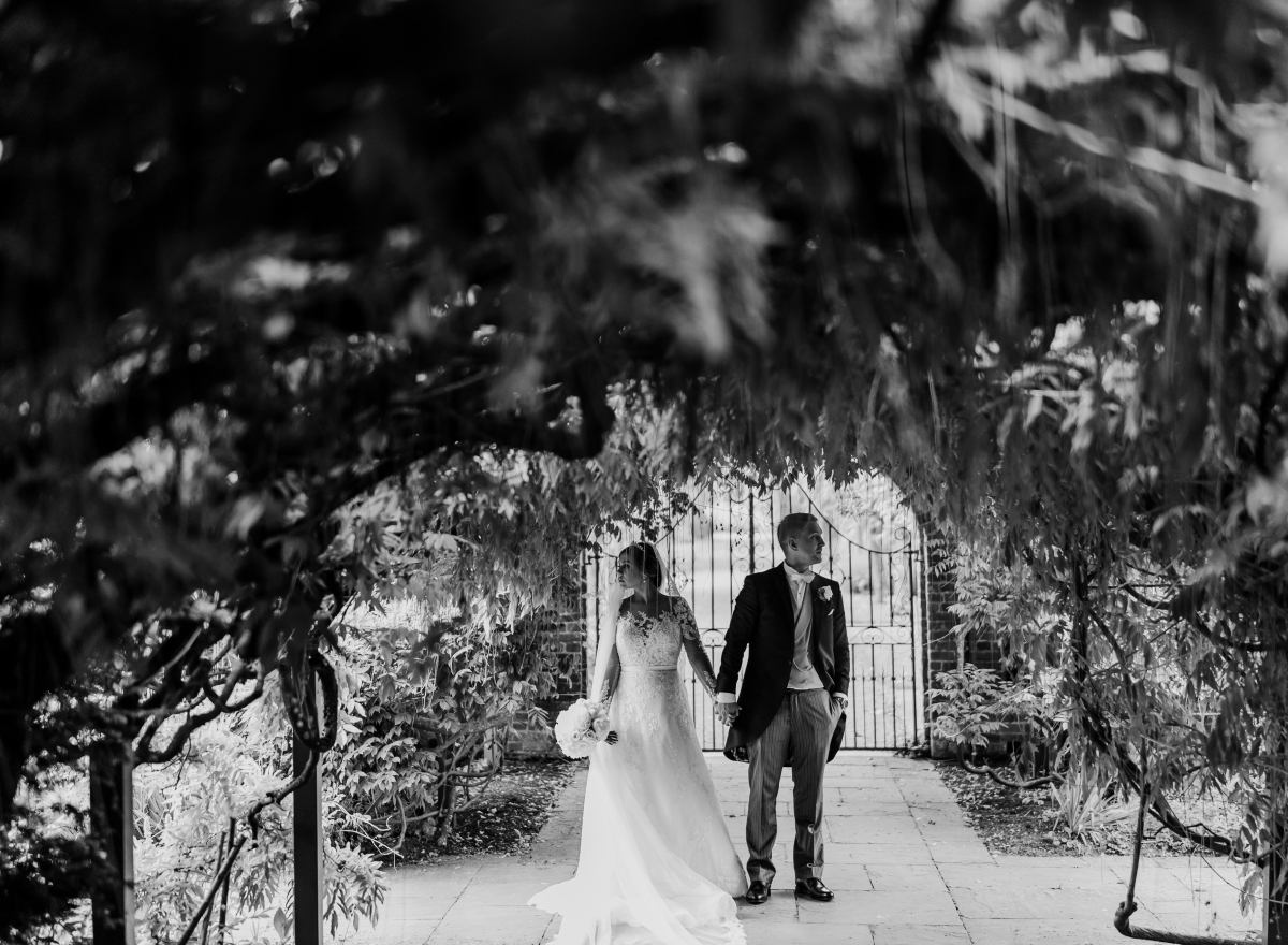 Black & white image of couple standing under wisteria arch