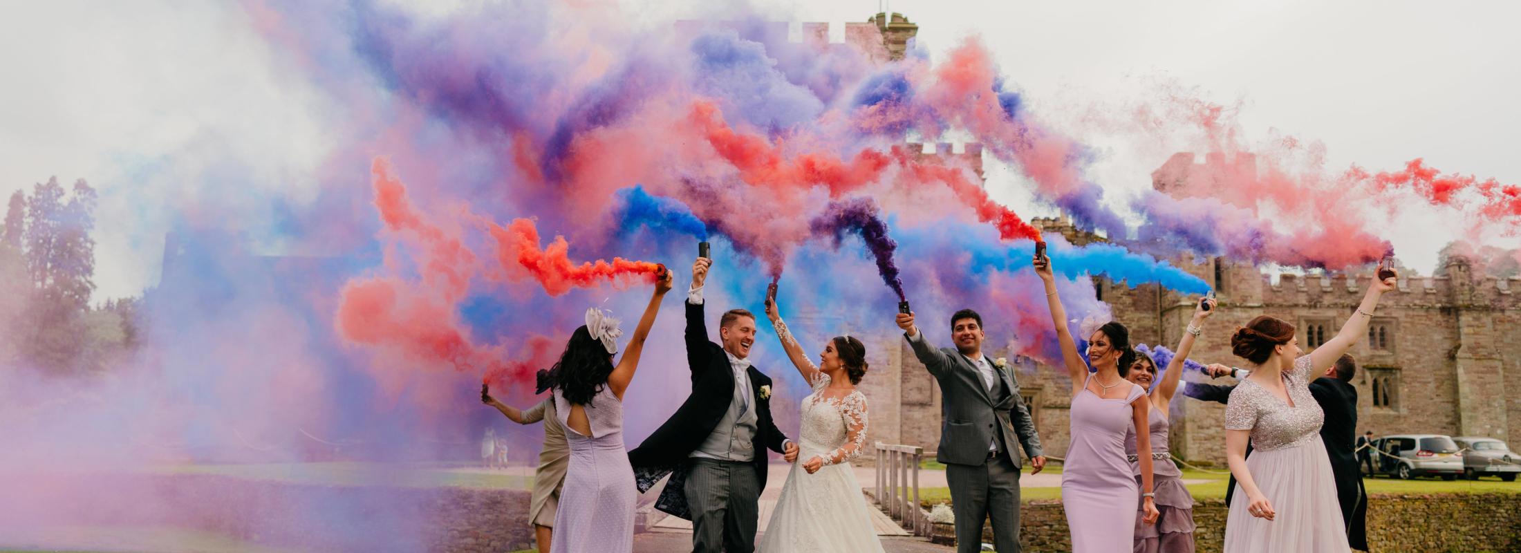 Wedding guests outside the castle with coloured smoke.