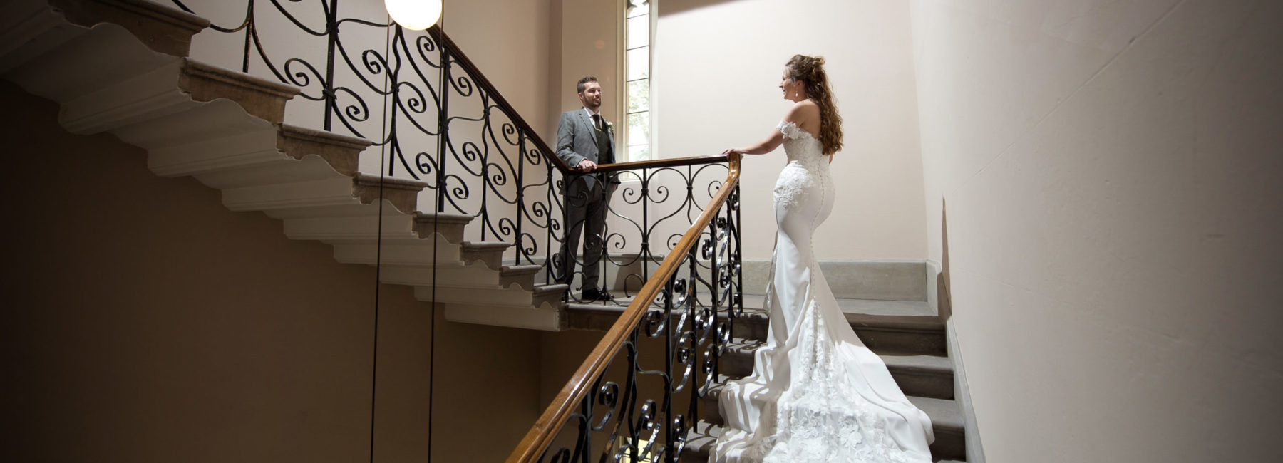 A bride and groom gaze at each other on the landing of a cantilevered staircase