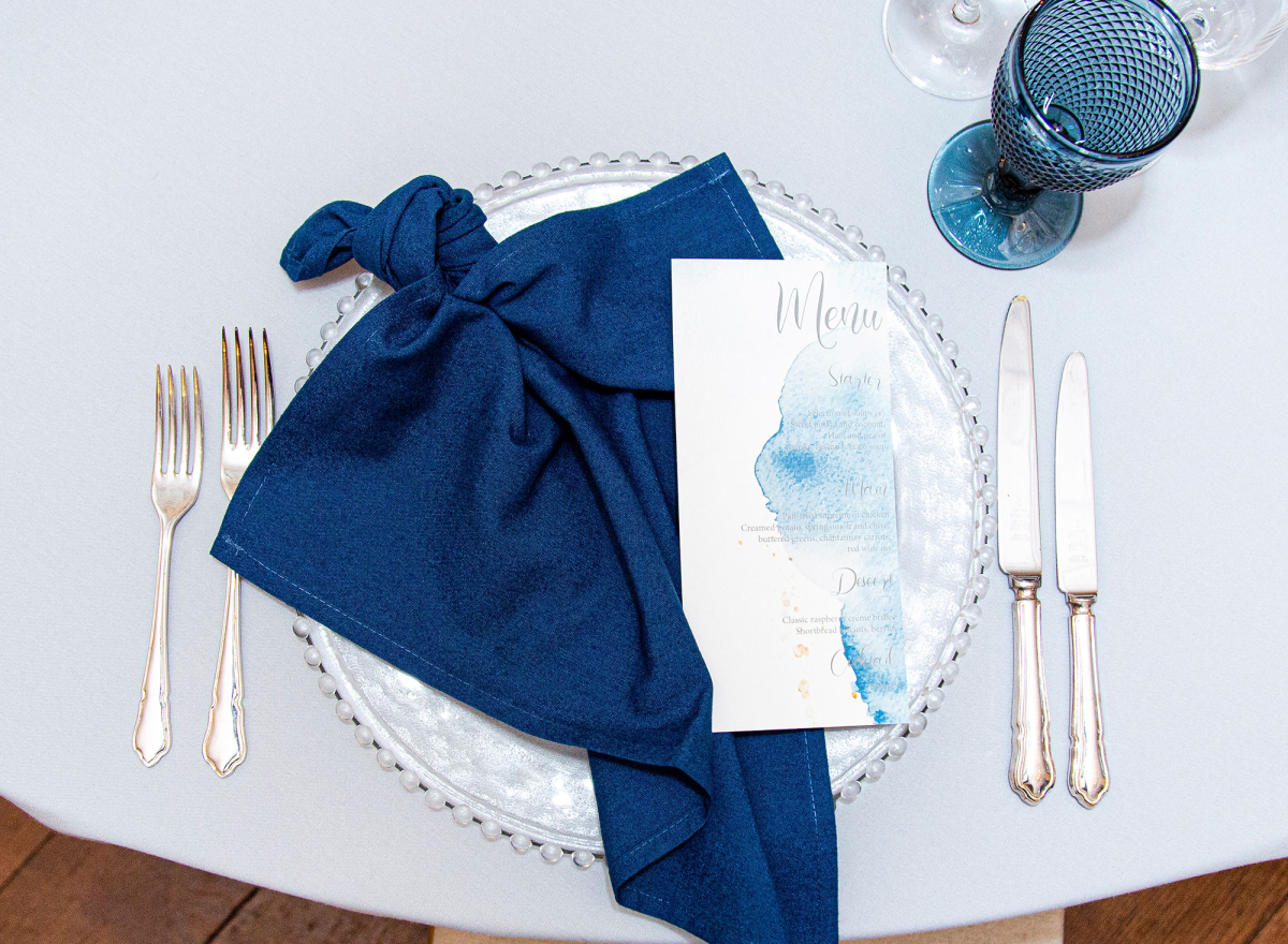 A blue napkin laid out over a place setting
