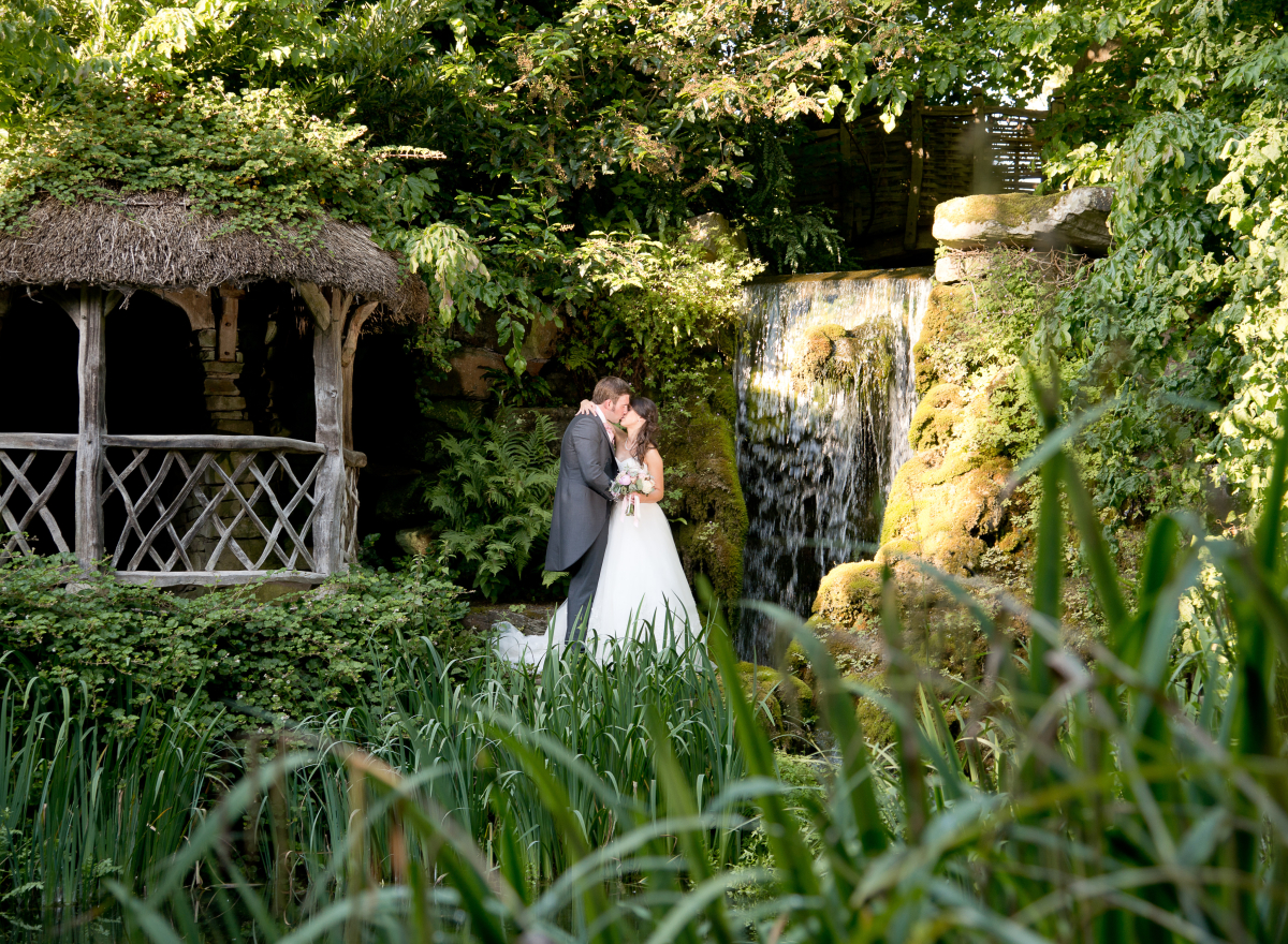 Couple kissing with shelter to left and waterfall to right in green garden.
