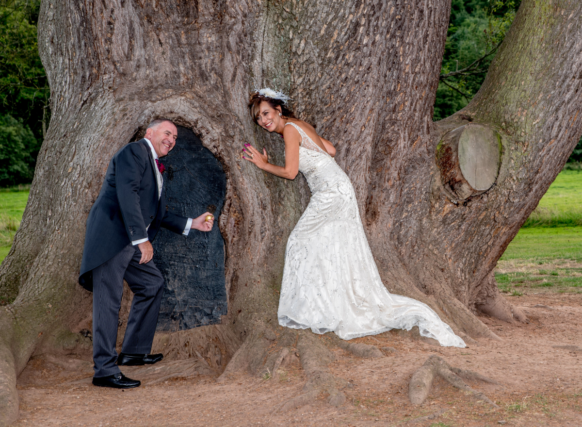 Couple stand by large tree pretending to open small door and listening to the tree.