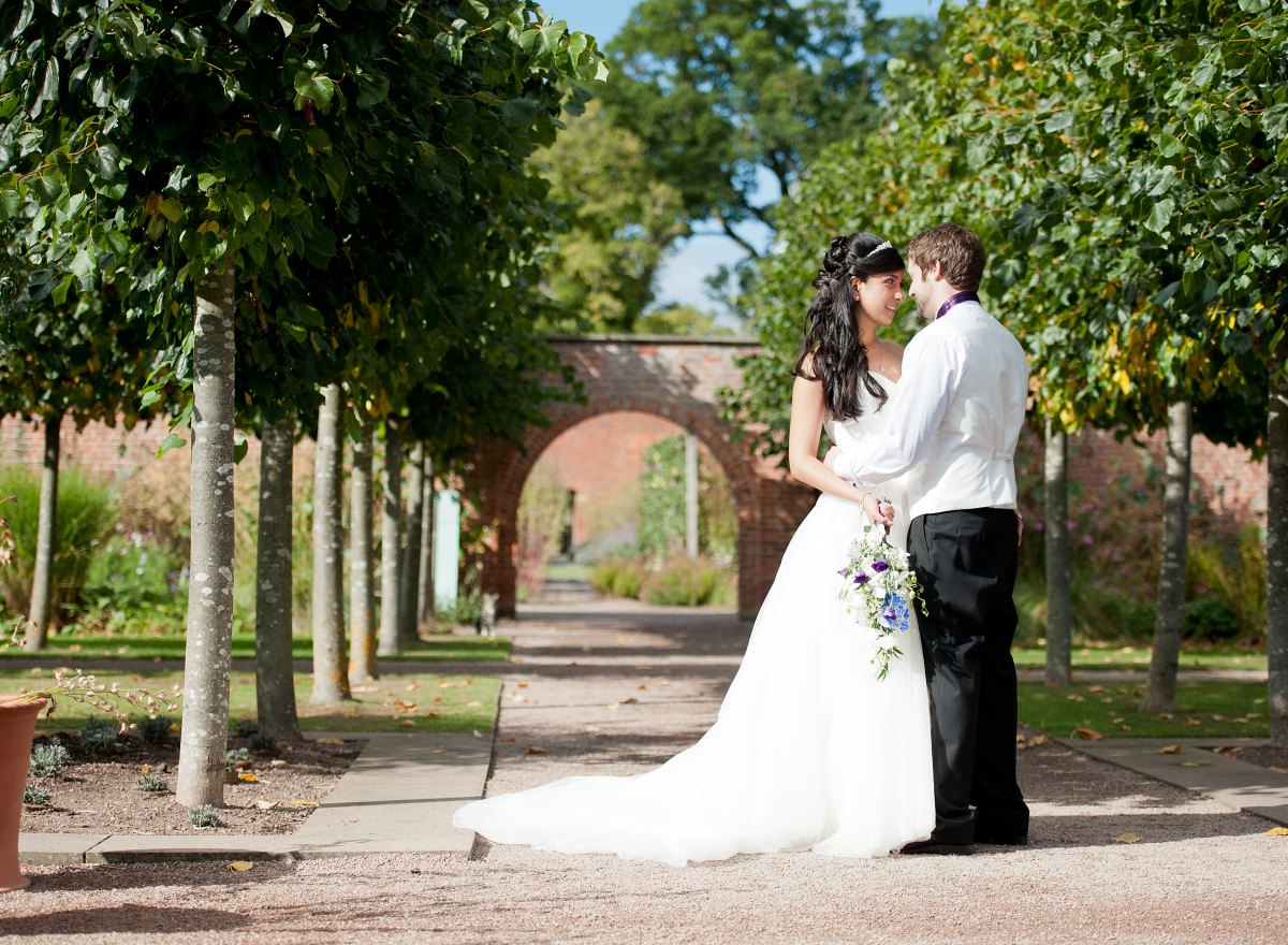 Couple looking at each other surrounded by an avenue of trees