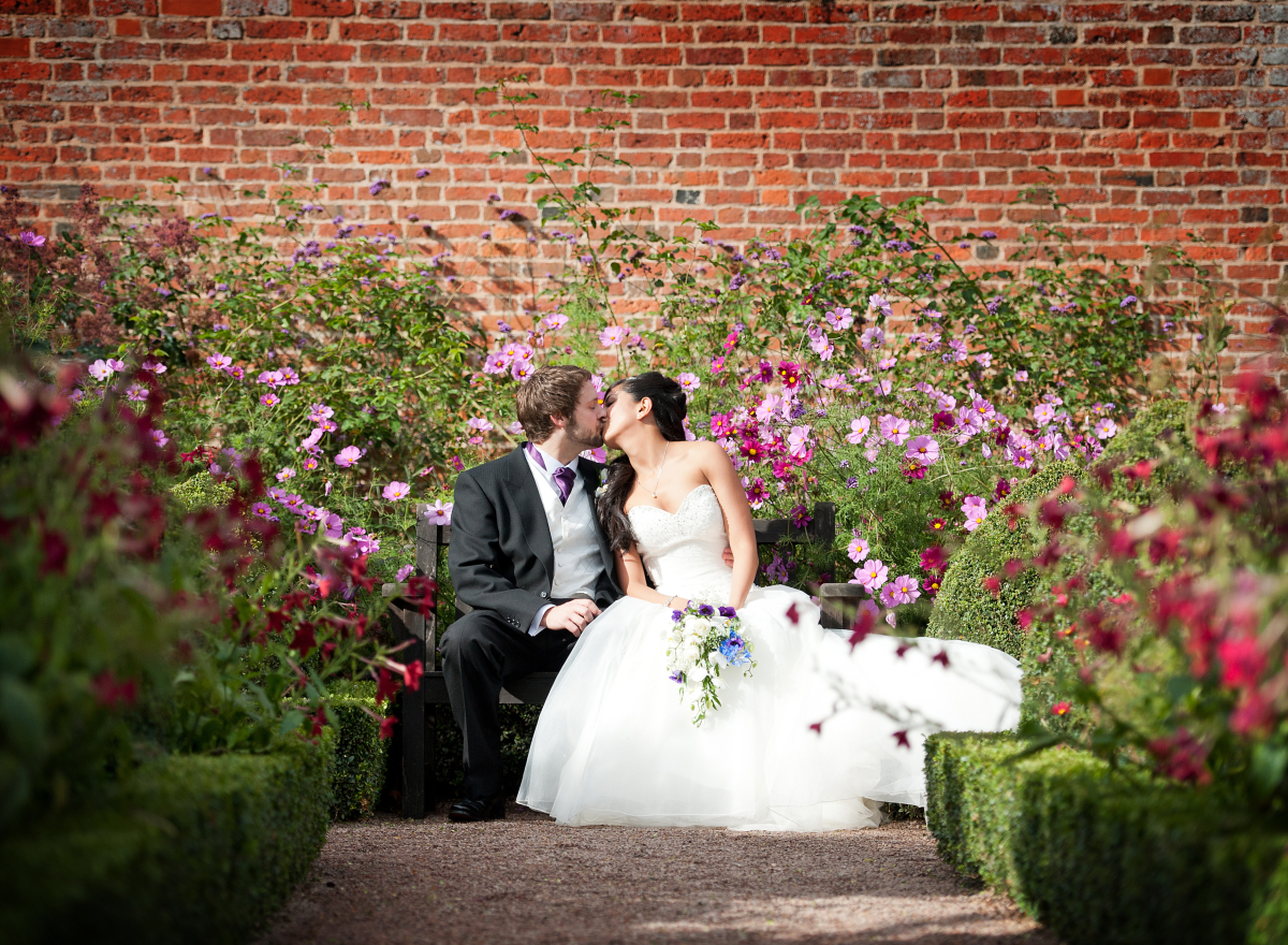 A bride and groom kiss, sitting on a bench surrounded by flowers