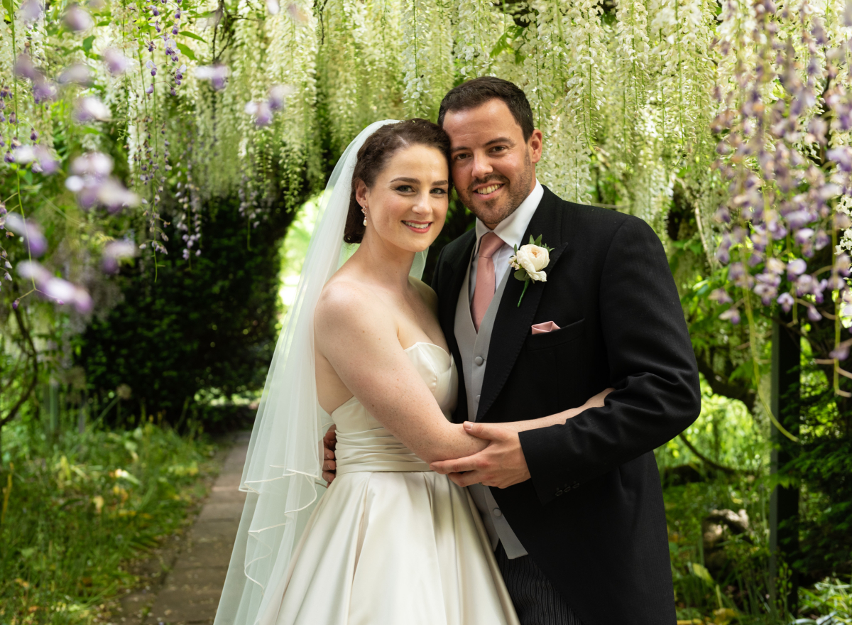 Couple under wisteria arch