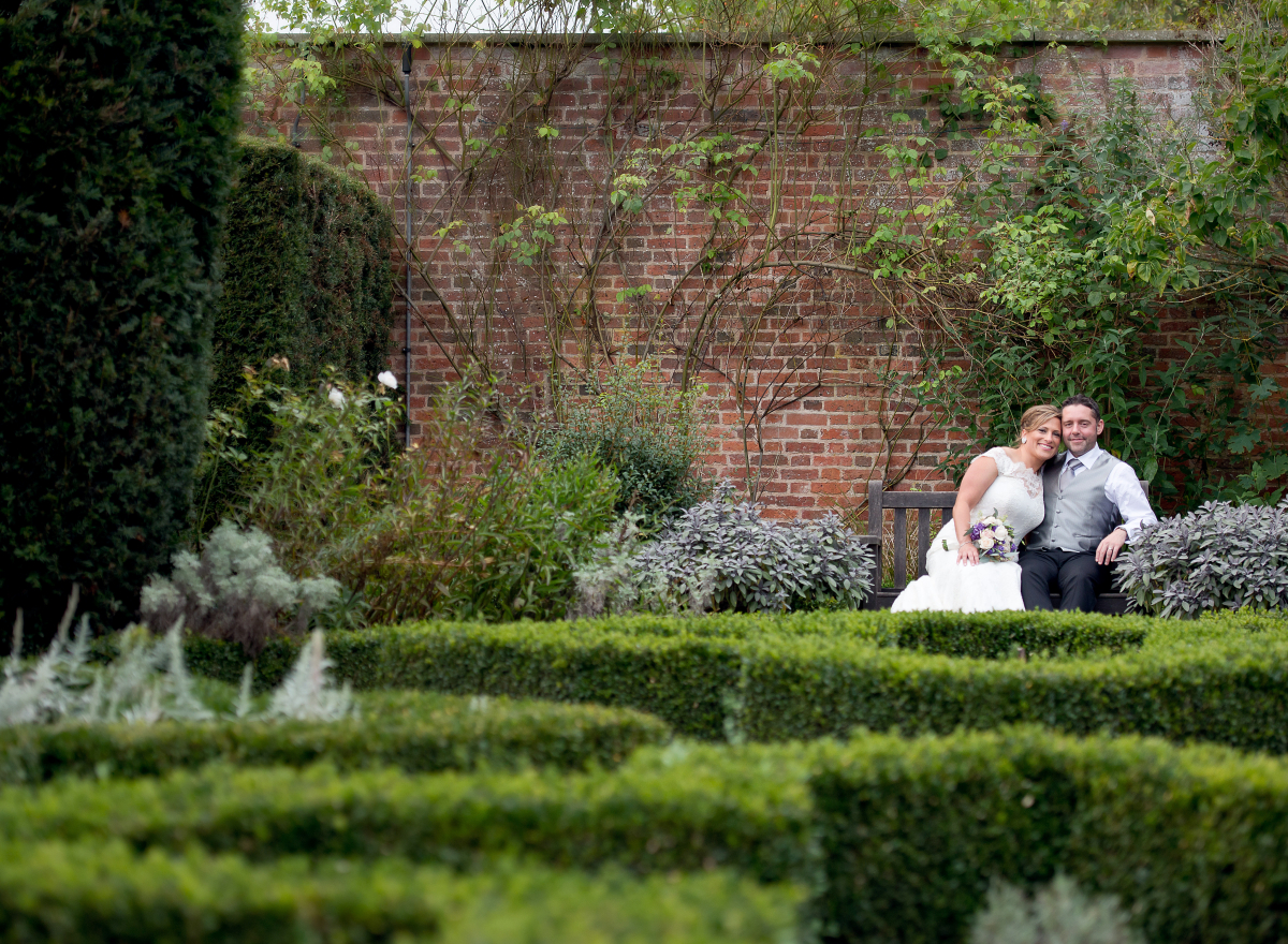 Couple on a bench in walled garden with box hedges