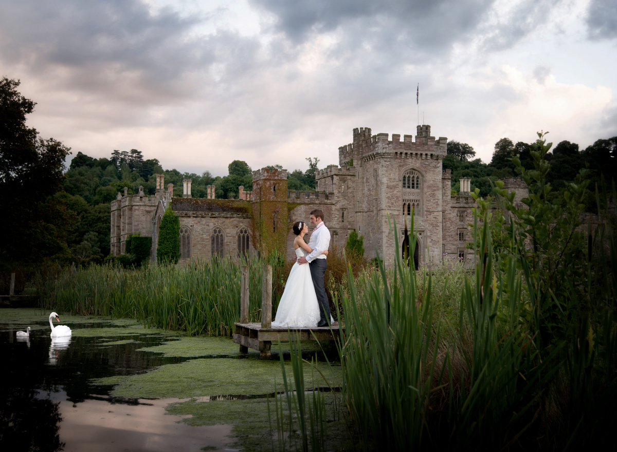 A bride and groom embrace in front of a castle. A swan and cygnet are watching from the lake.