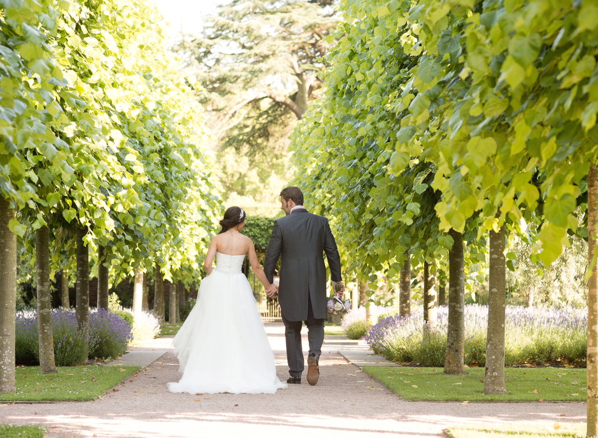 Couple walking away from camera down avenue of trees