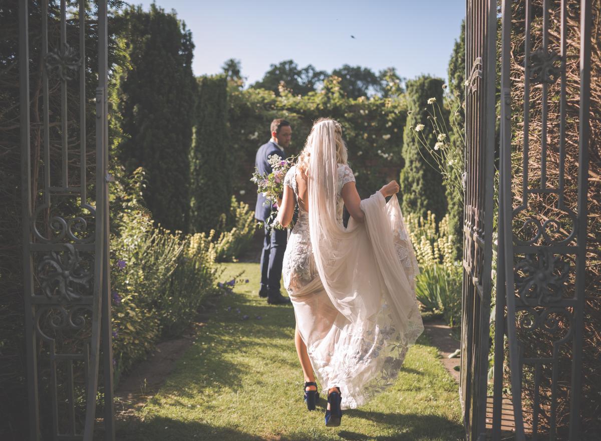 Wedding couple walking into the gardens