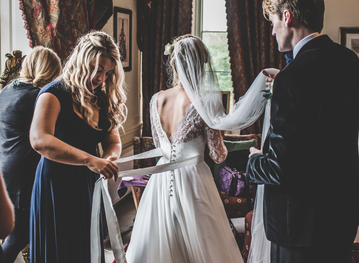 A bride getting dressed, assisted by her friends