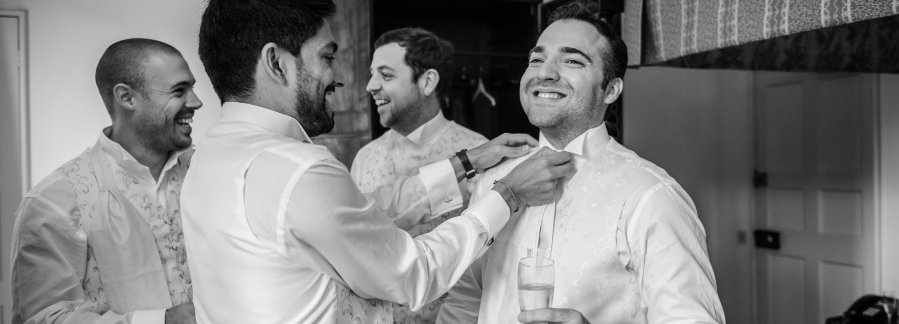 A group of men laughing, preparing for a wedding