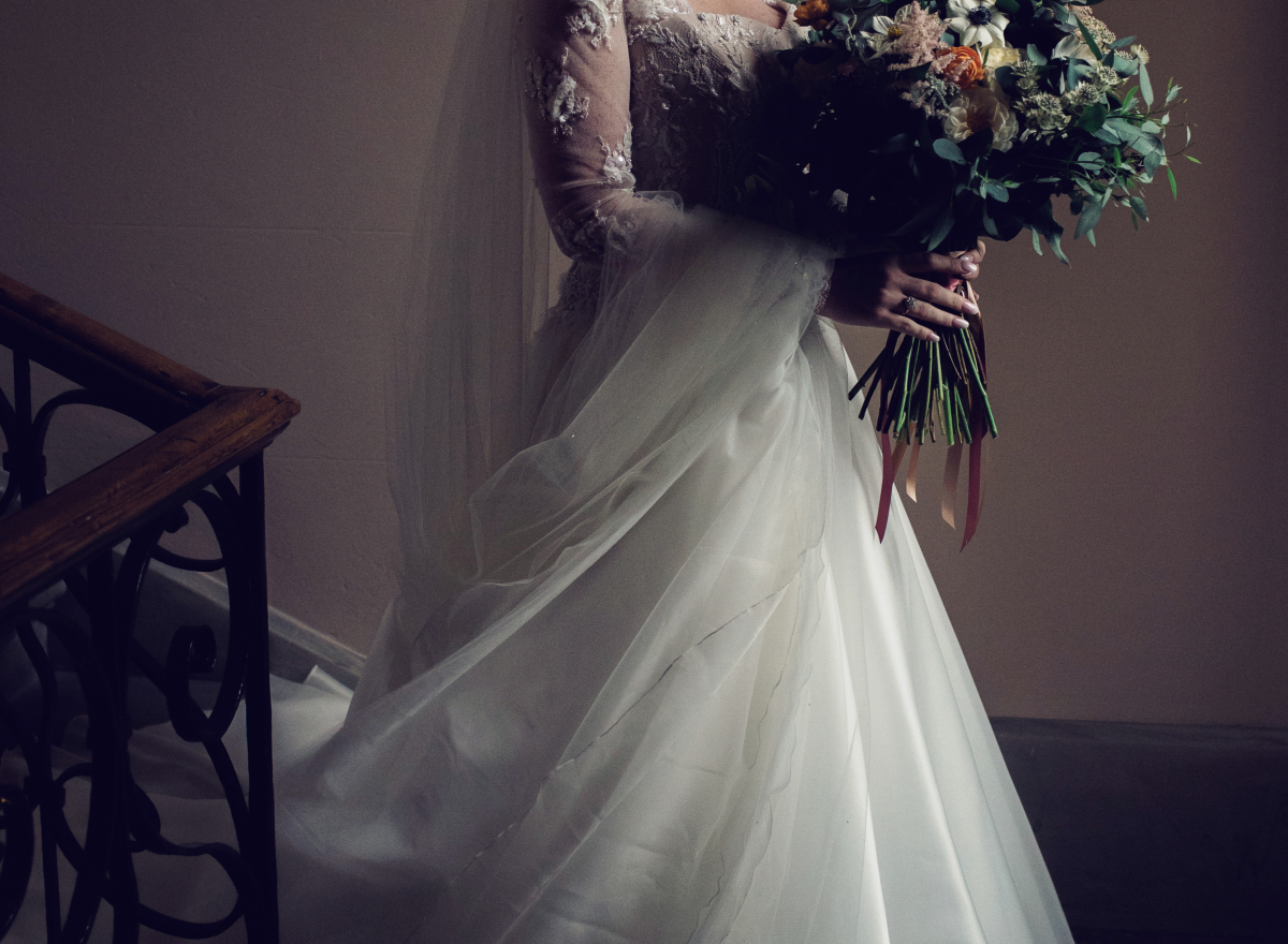 A bride, carrying a bouquet, walks down the stairs