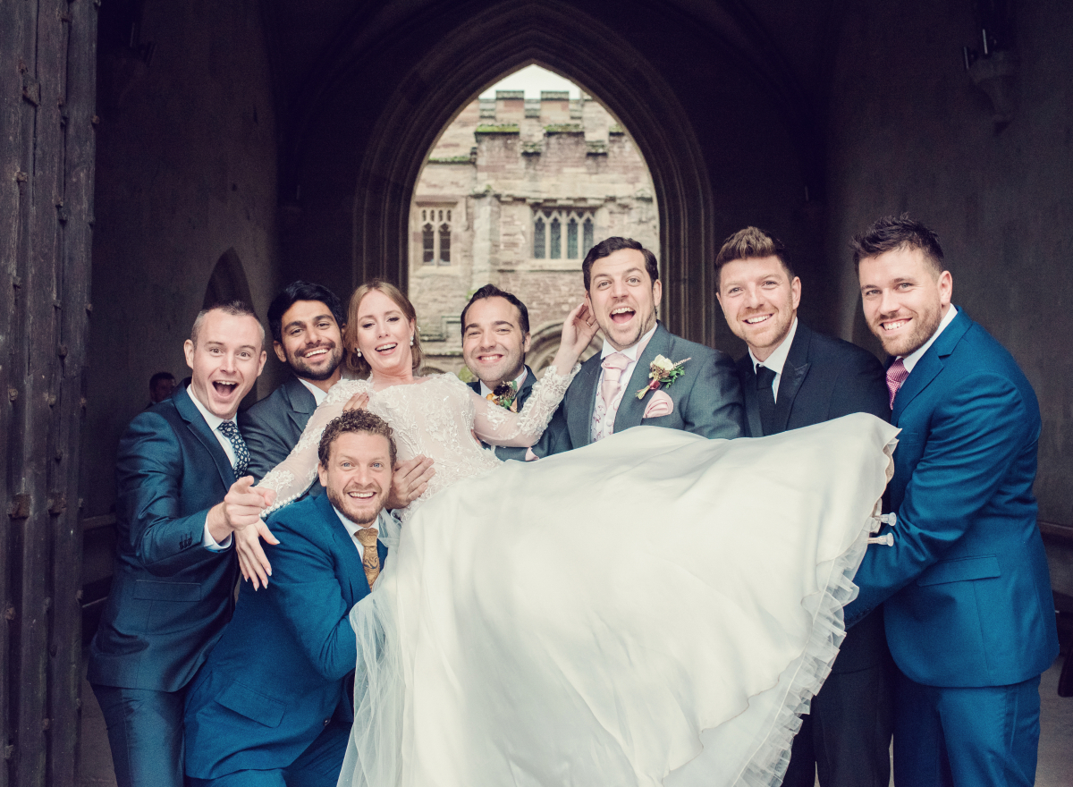 A groom and his groomsmen lifting a bride in front of them.