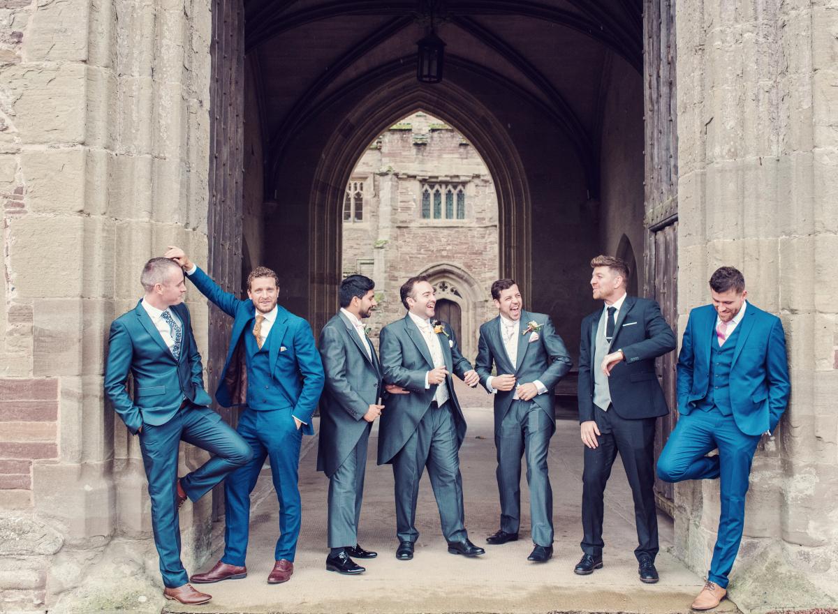 A groom and his groomsmen laughing in a castle doorway