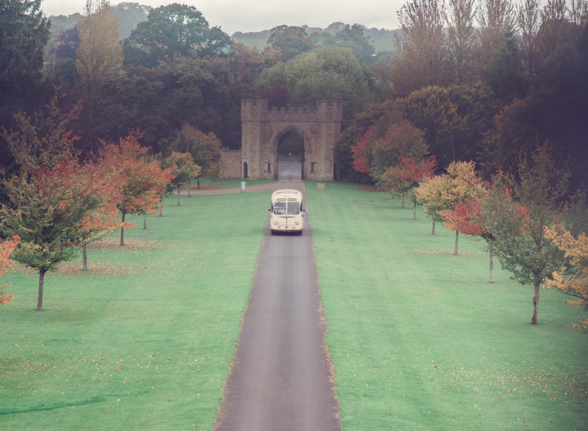 Bus arriving along driveway in the autumn with colourful trees