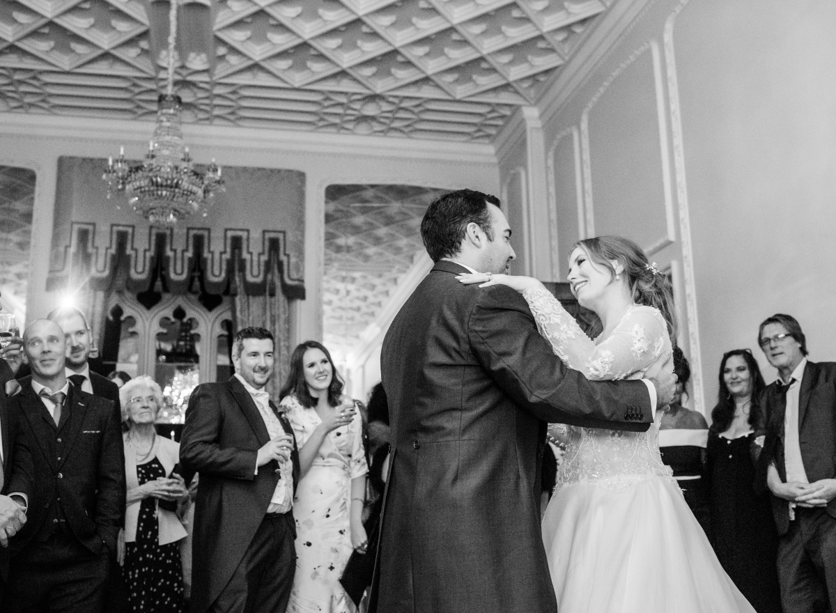 A black and white photo of a bride and groom dancing