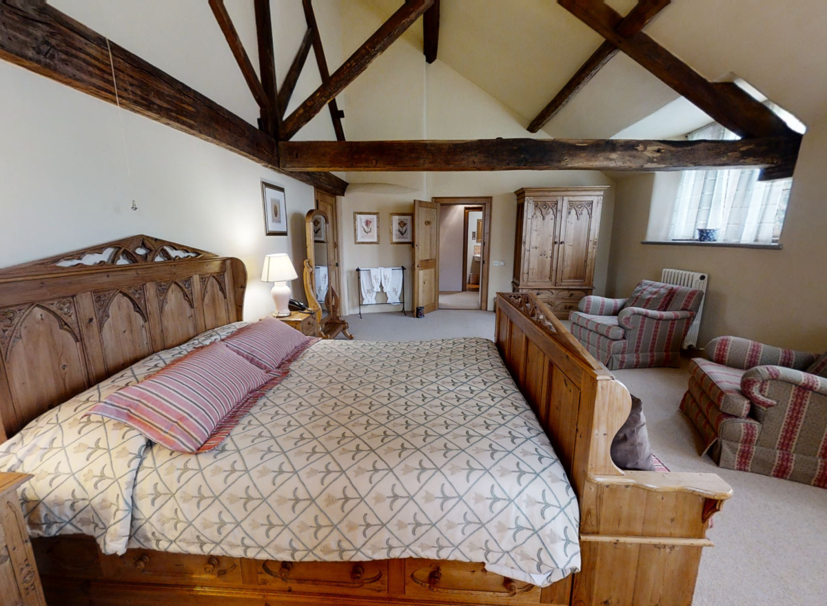 Large bedroom with double bed and beamed ceilings.