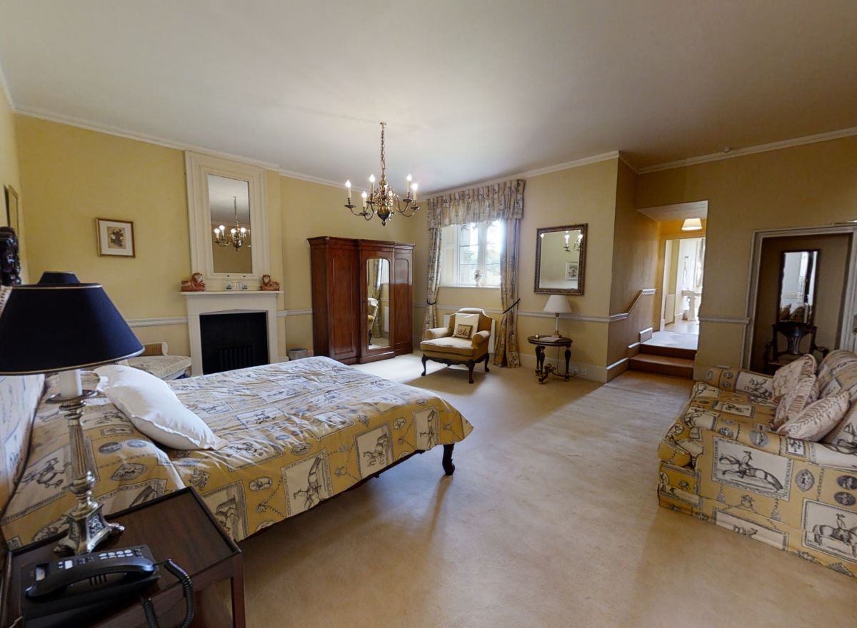 Yellow bedroom with double bed, chandelier and beautiful furniture.