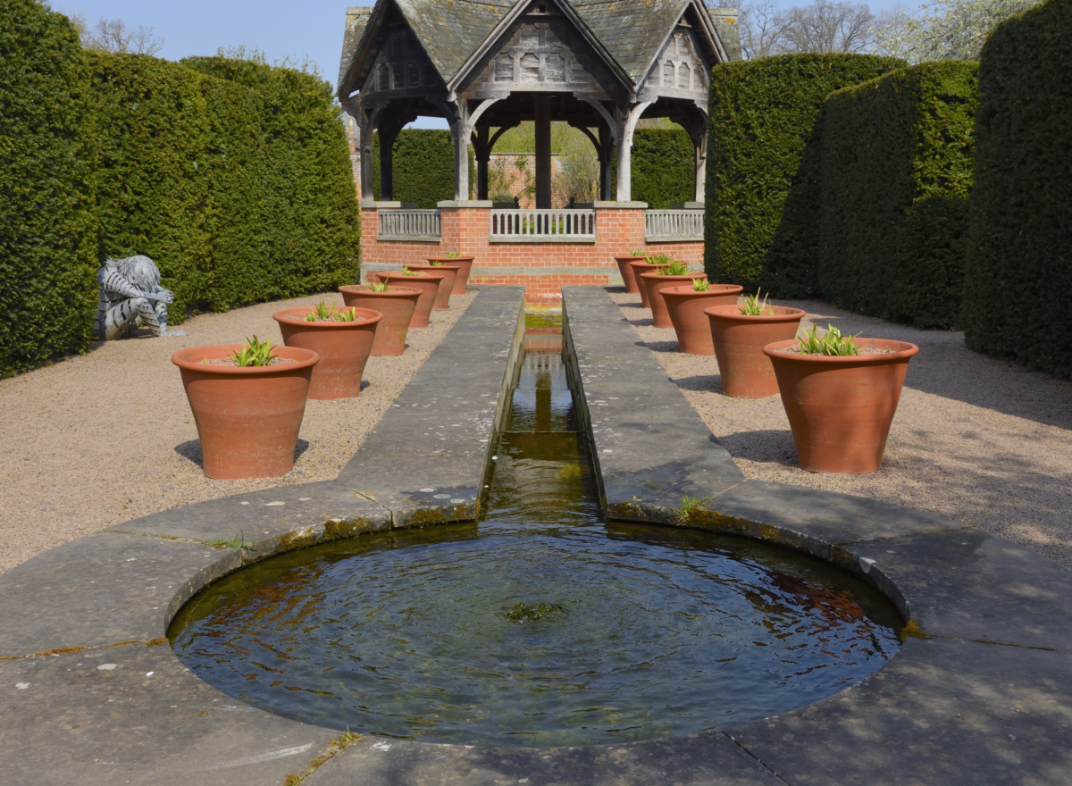 A circular water feature, leading down in a narrow channel to a pavilion