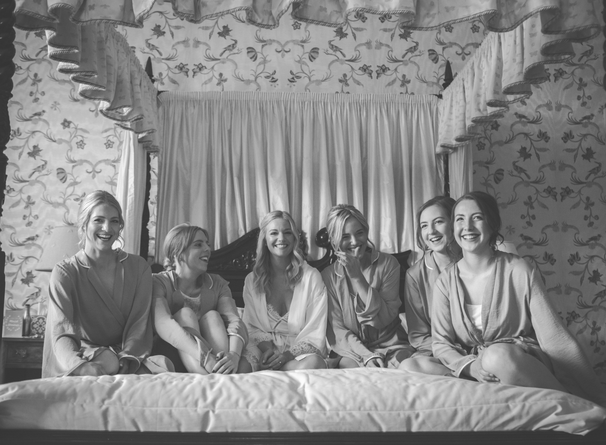 Black and white photo of bride and bridesmaid sitting on bed