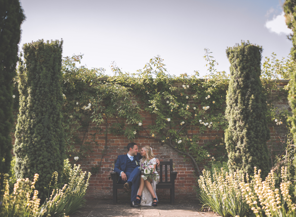 Couple on a bench surrounded by roses and brick wall